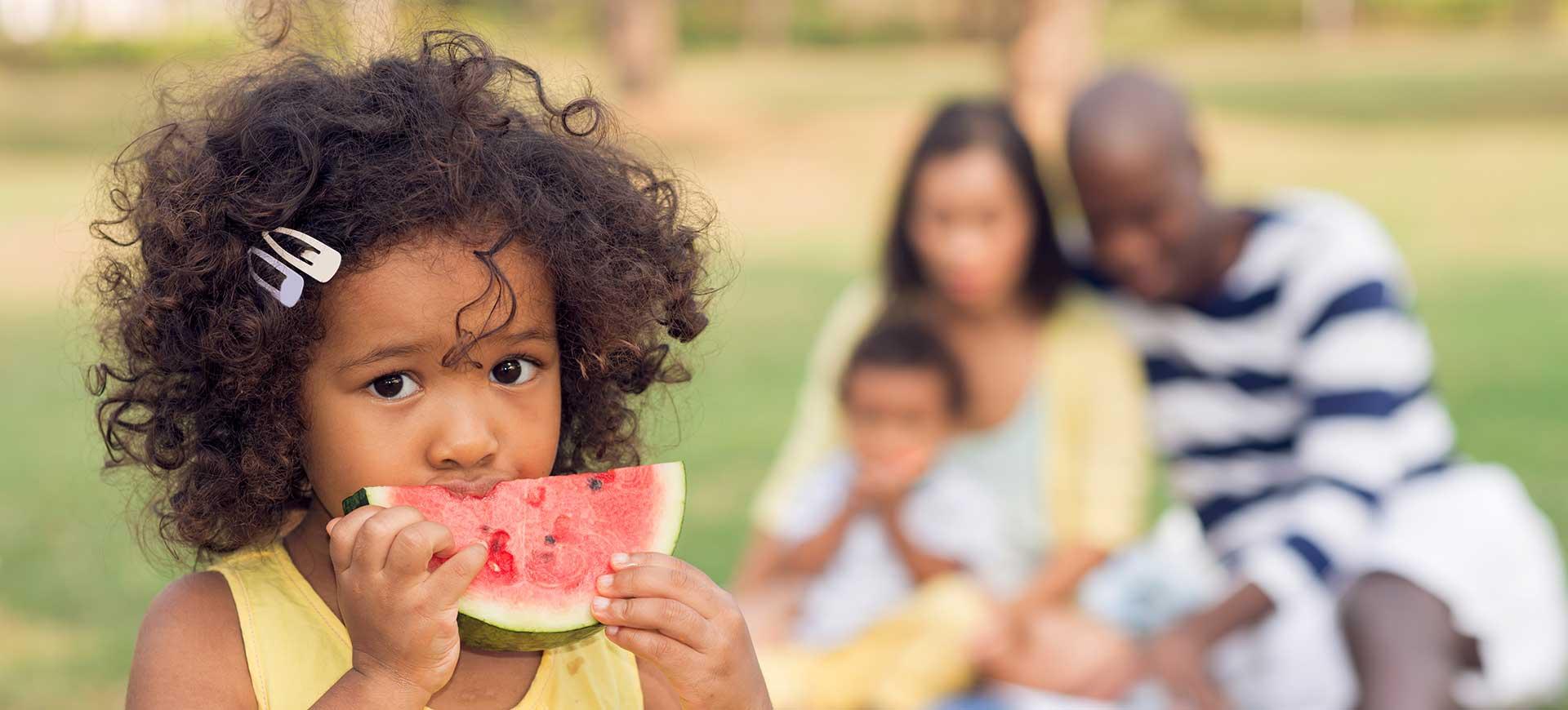 Une fillette mange une pastèque